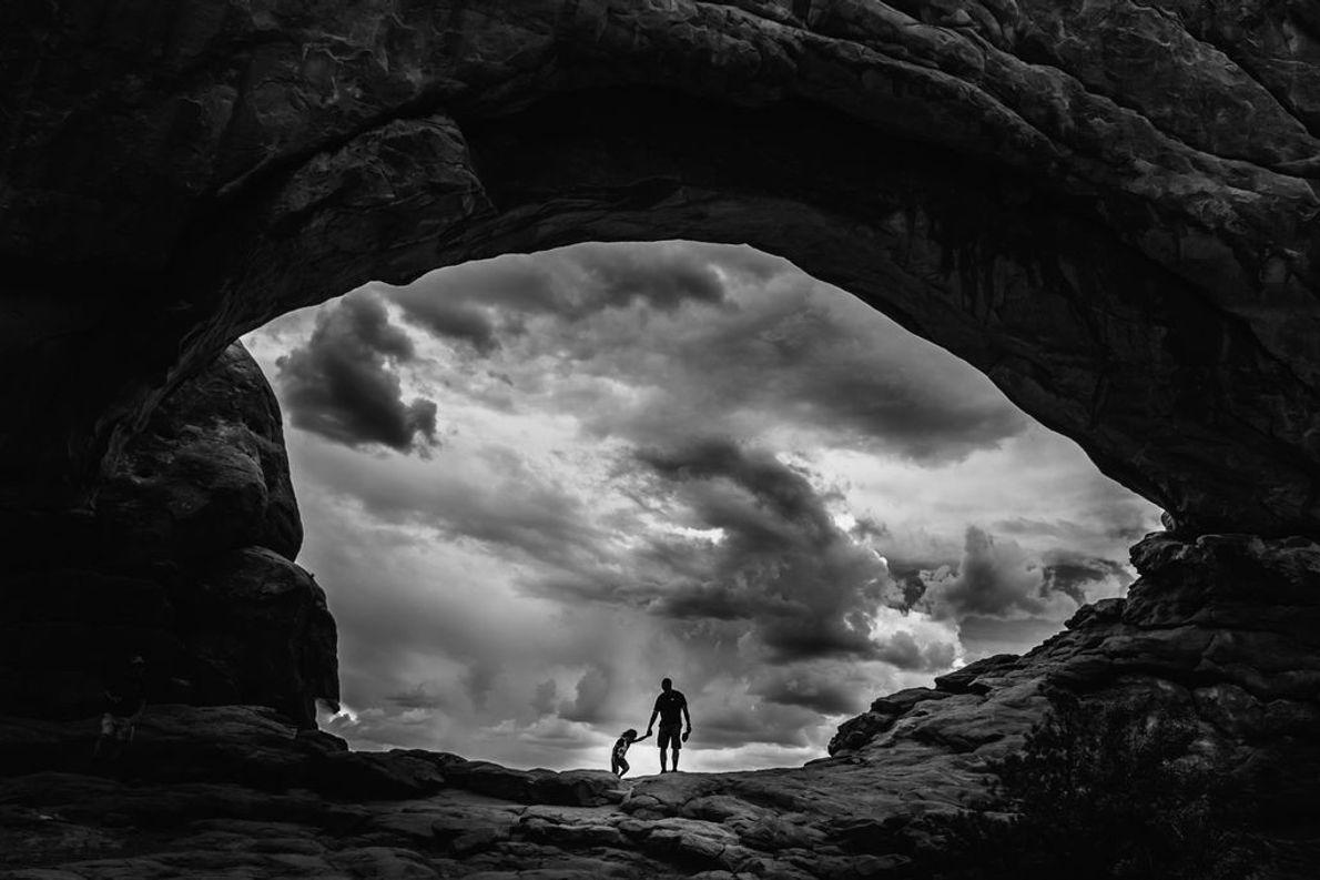 Vater und Sohn beobachten die aufziehenden Gewitterwolken im Arches-Nationalpark in Utah, USA.