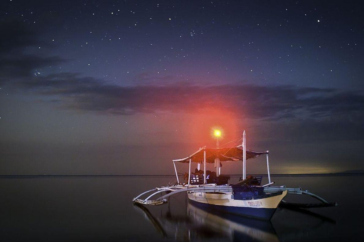 Vor der philippinischen Insel Calangaman Island sehen sich Menschen die Sterne an, während das Boot auf ...