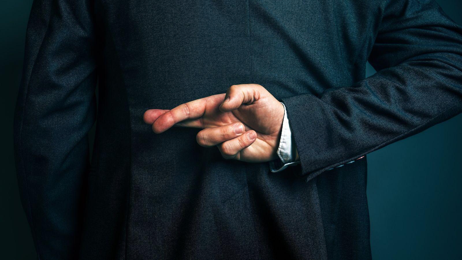 Mann verkreuzt die Finger hinter dem Rücken