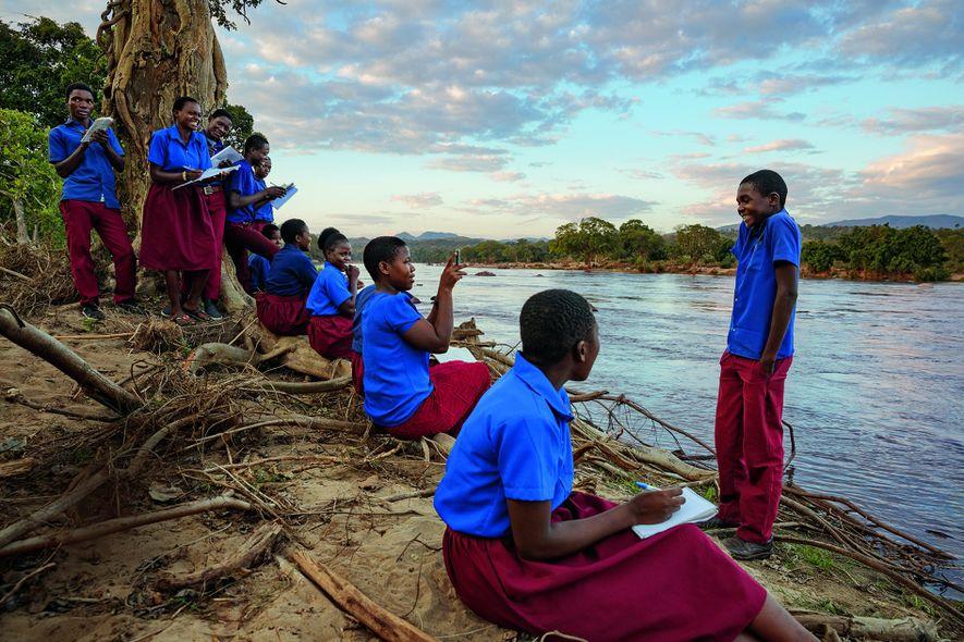 Majete Wildlife Reserve in Malawi: Diese Schüler machen am Ufer eines Flusses Pause. Ihr Besuch in ...