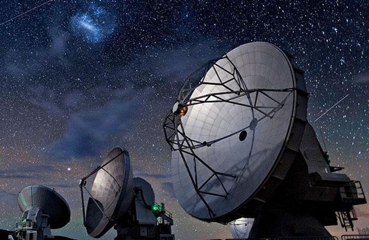 Die Große Magellansche Wolke (oben Mitte) leuchtet am Himmel über sechs Antennenschüsseln des Atacama Large Millimeter/submillimeter …
