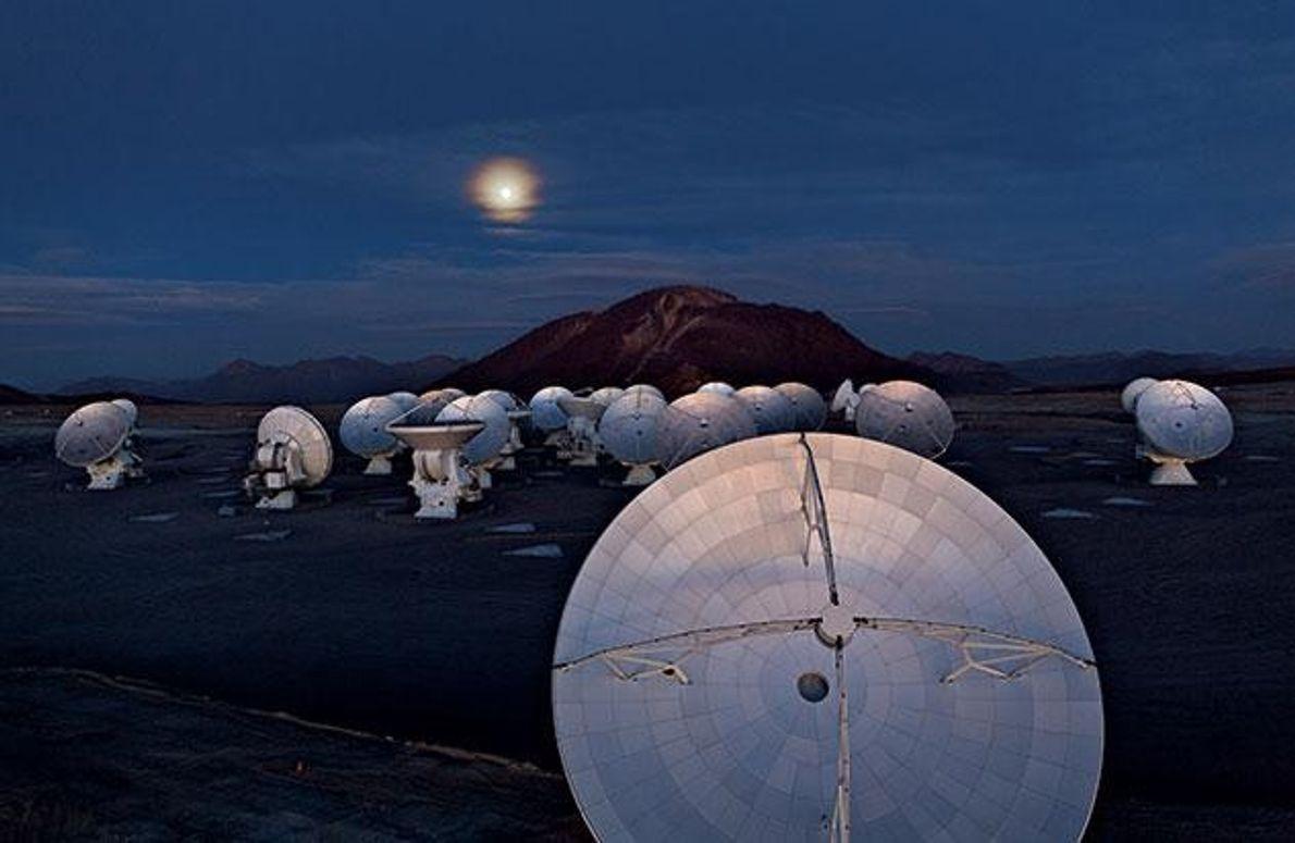 """Auf einem Hochplateau in der chilenischen Atacamawüste beleuchtet die Sonne am Horizont einige Antennen von """"Alma"""" …"""