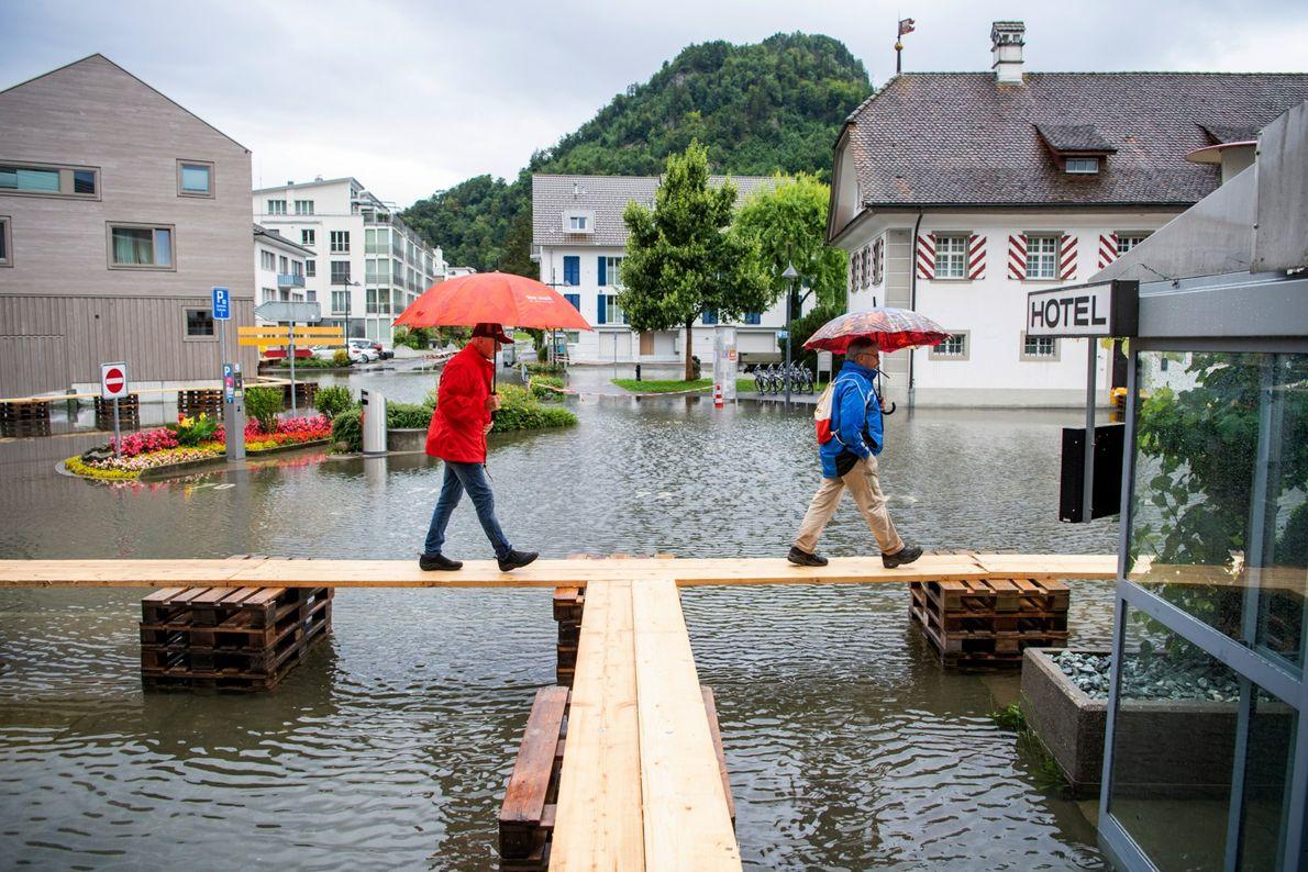 In der Schweiz nutzen Fußgänger provisorische Holzbrücken, um den überfluteten Dorfplatz zu überqueren.