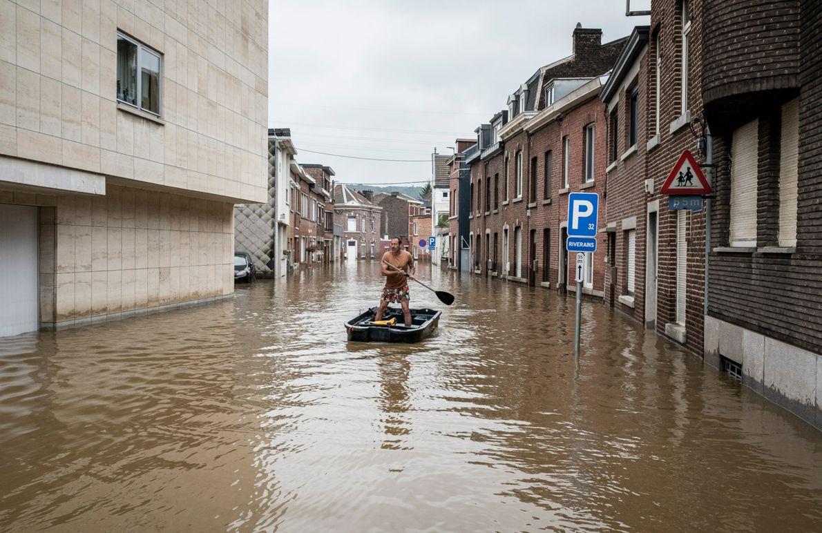Ein Mann rudert am 16. Juli 2021 mit seinem Boot durch ein Wohngebiet in Belgien.