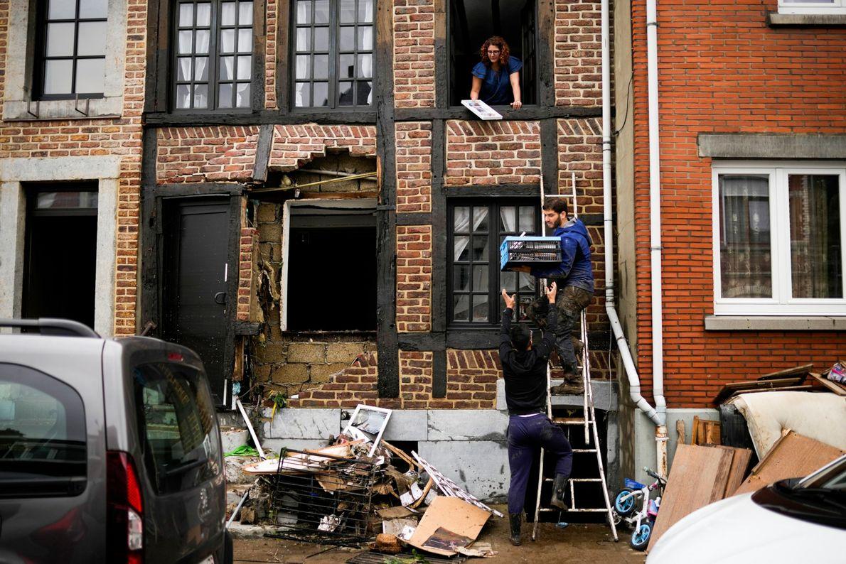 Nachdem das Hochwasser zurückgegangen ist, versuchen die Menschen ihren Besitz zu retten.