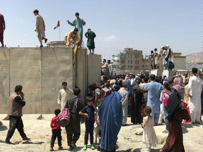 Am 16. August 2021 versuchen Menschen auf der Flucht vor den Taliban verzweifelt, über die Mauer ...
