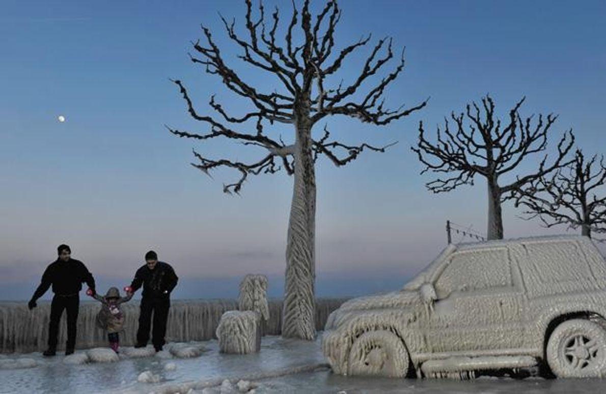 Gefrorene Gischt aus dem Genfer See hüllt im Februar 2012 Autos, Bäume und Uferstraße in einen …