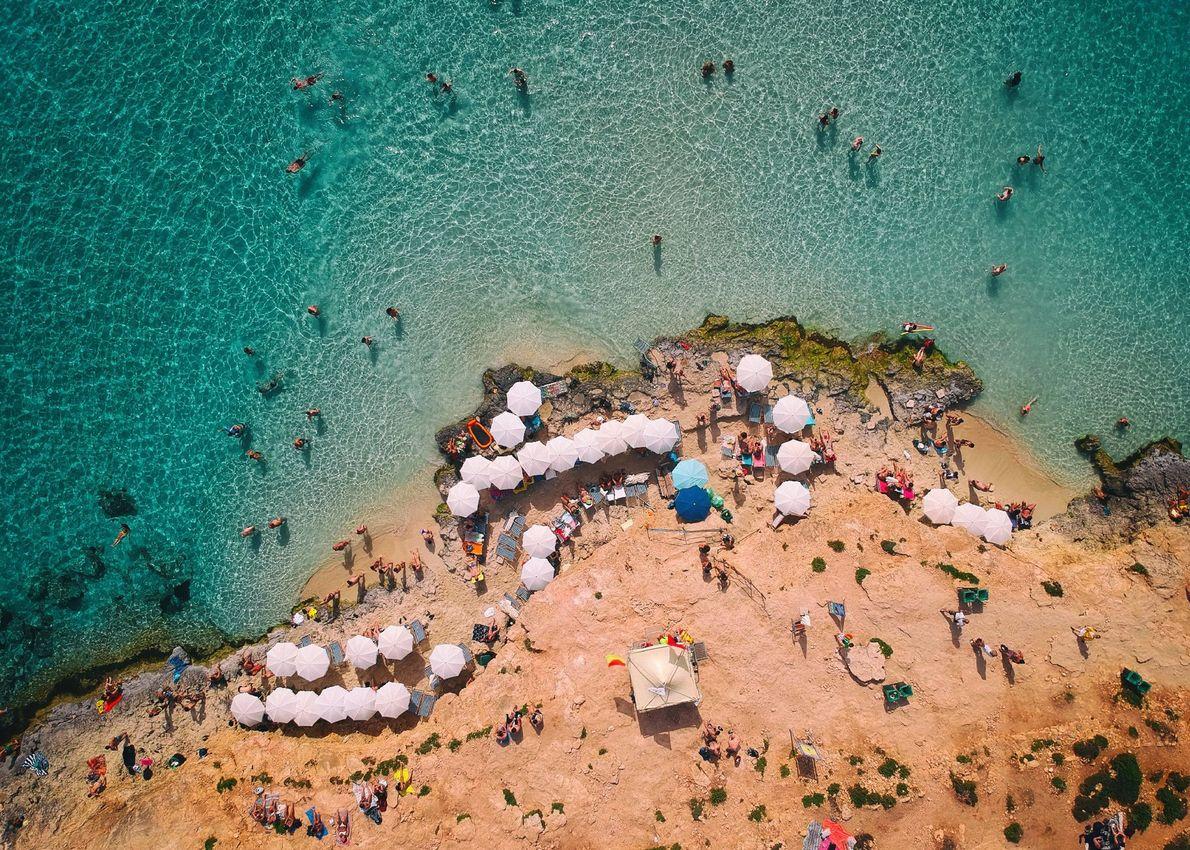 Schwimmer waten in eine blaue Lagune zwischen den maltesischen Inseln Comino und Cominotto. Erstere war einst ...