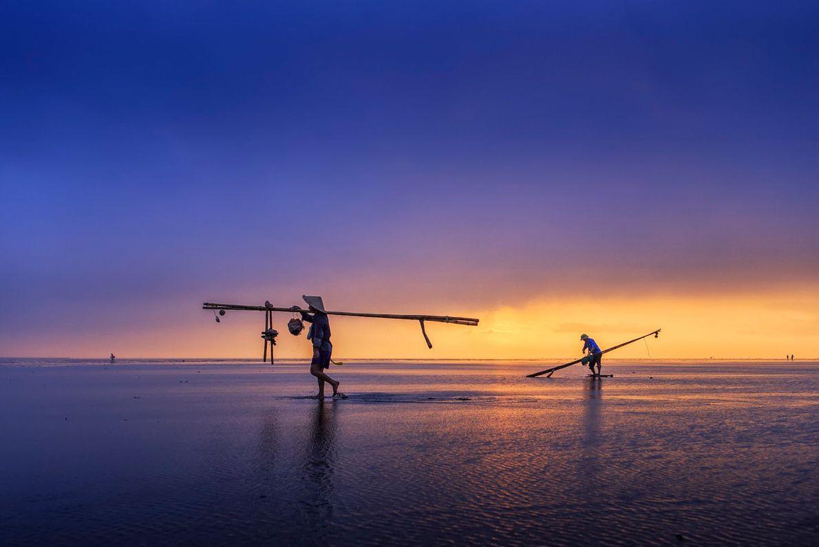 Fischer in Thai Binh, Vietnam, tragen ihre Angelruten und Netze auf ihren Schultern nach einer Sturmwarnung ...