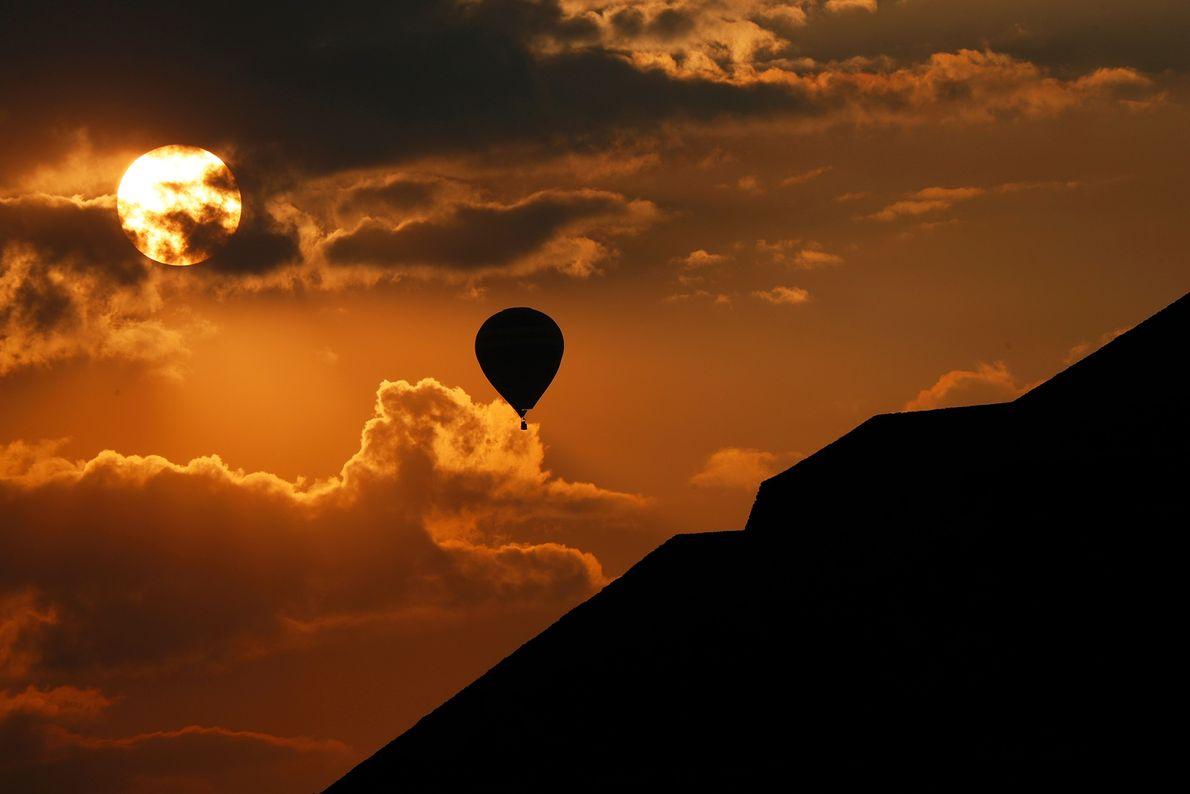 Zur Tagundnachtgleiche am 21. März hängt die Sonne wie eine goldene Kugel über der Sonnenpyramide von ...