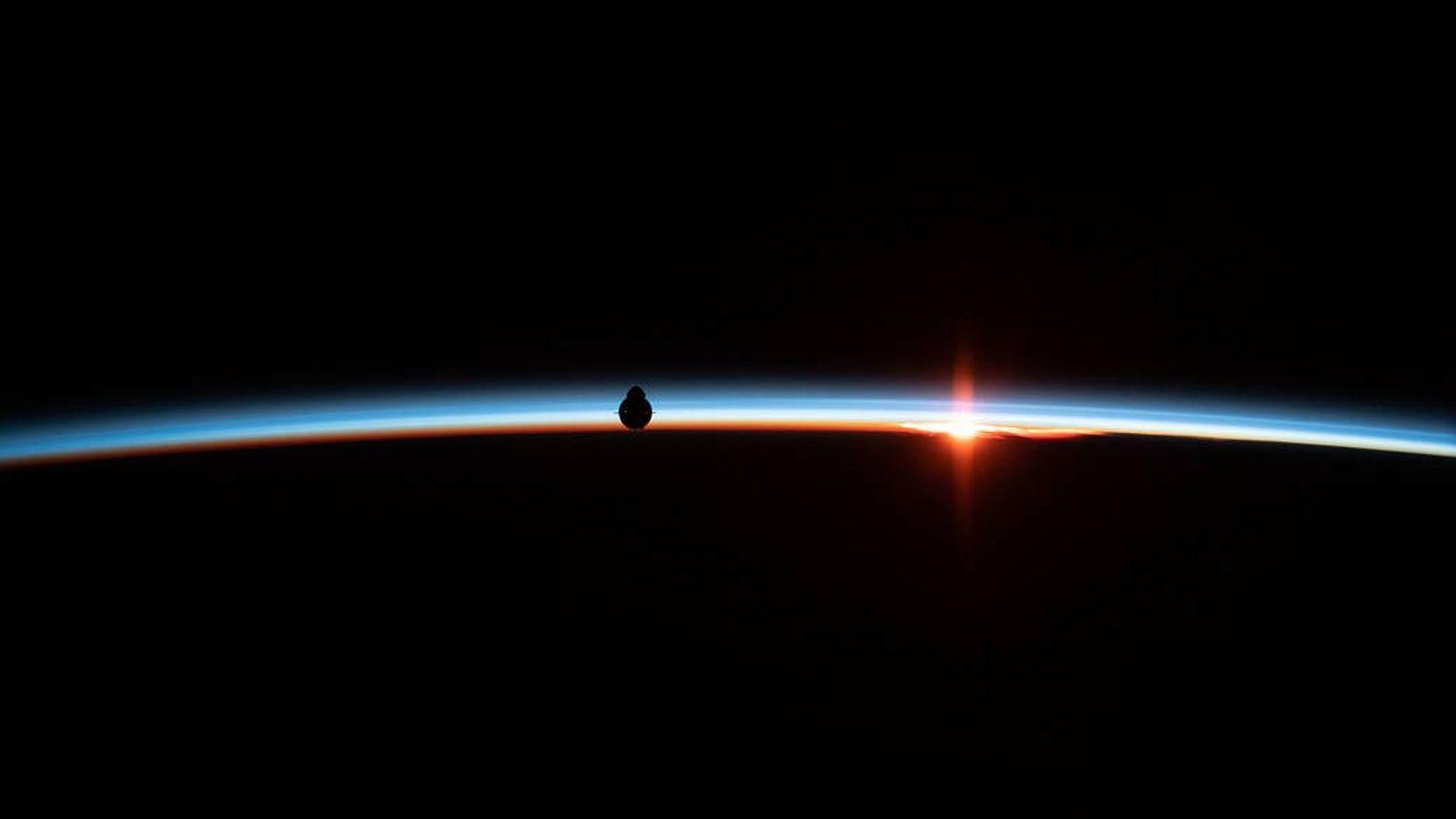 Die Silhouette des unbemannten SpaceX-Raumschiffs Dragon hebt sich vor dem leuchtenden Horizont der Erde ab. Die ...