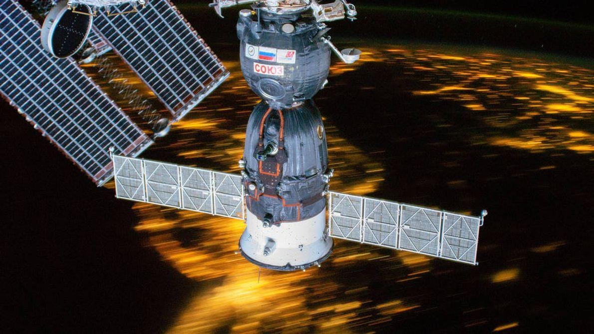 Die Sojus MS-12, die an der ISS angedockt ist, gleitet mitsamt der Raumstation über die verschwommenen ...