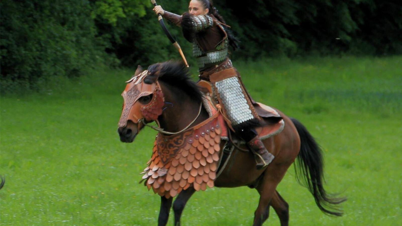 In Kampfoutfit schießt Pettra Engeländer mit Pfeil und Bogen vom Pferd