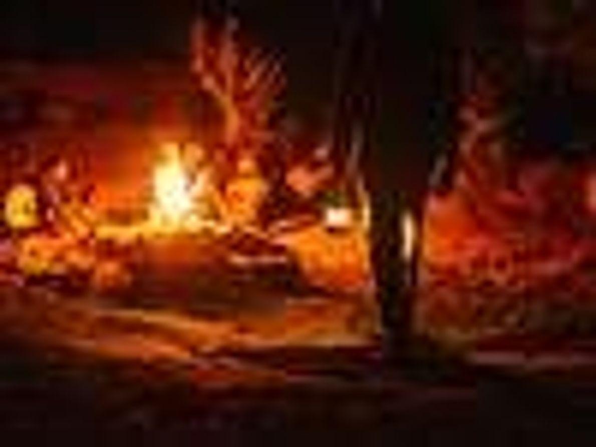 Bild mit Menschen am Lagerfeuer bei Nacht.