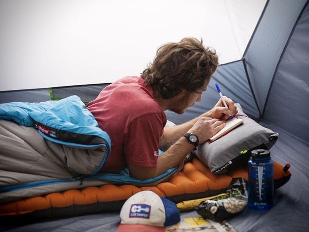 Bild eines schreibenden Mannes in einem Zelt.