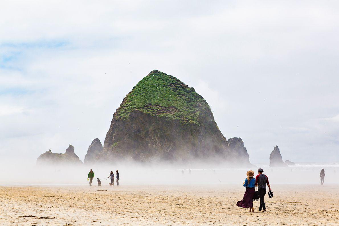 Foto von Leuten, die auf dem Cannon Beach in Oregon spazieren