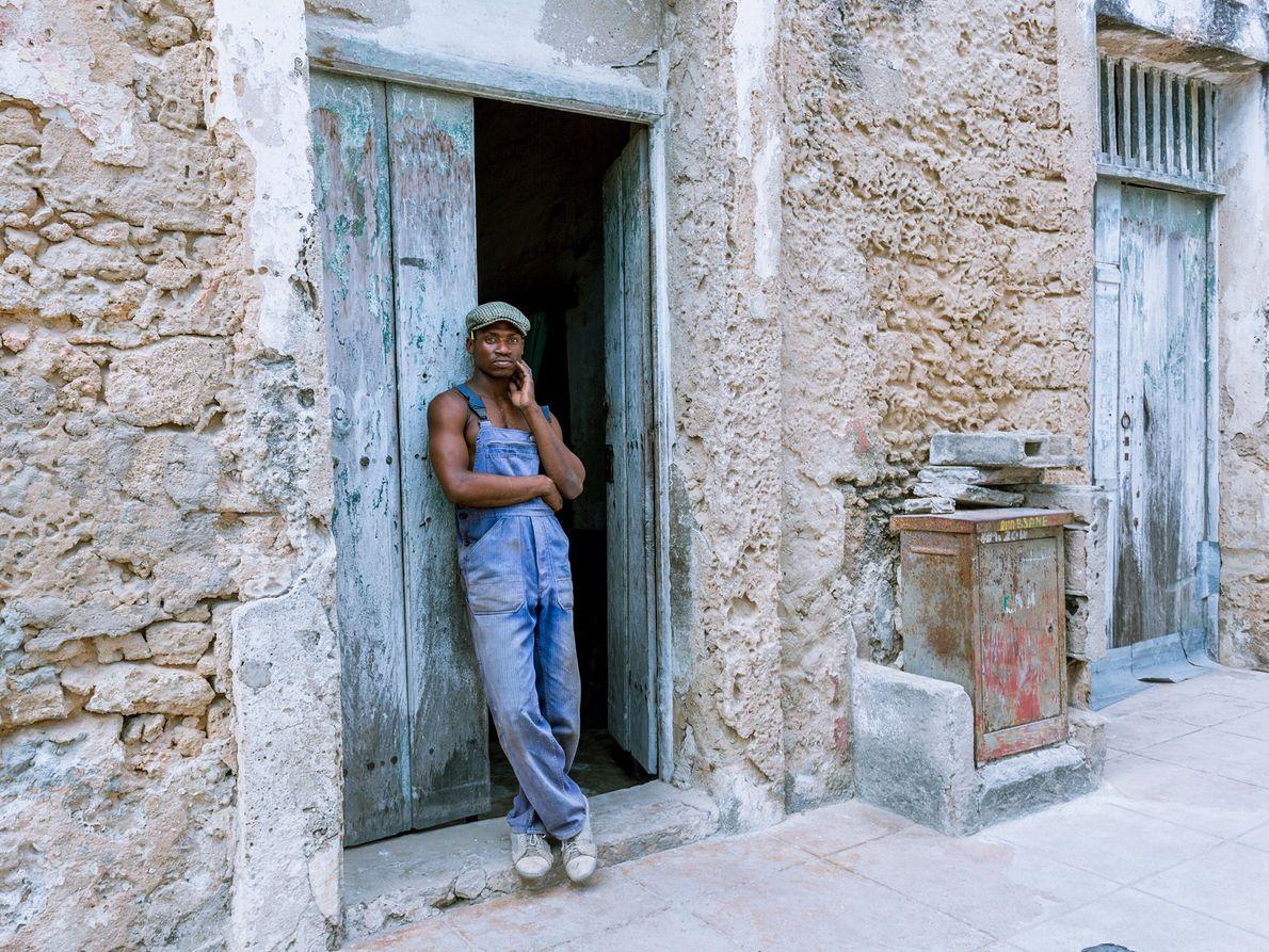 Ein Schreiner lehnt sich an die Tür seiner Werkstatt in Stone Town.