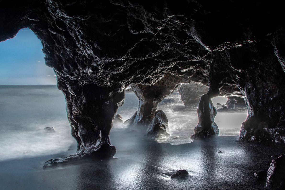 Ein paar Sonnenstrahlen betonen die knotige Struktur der Kalksteinwände in diesen Höhlen an einem Strand auf ...
