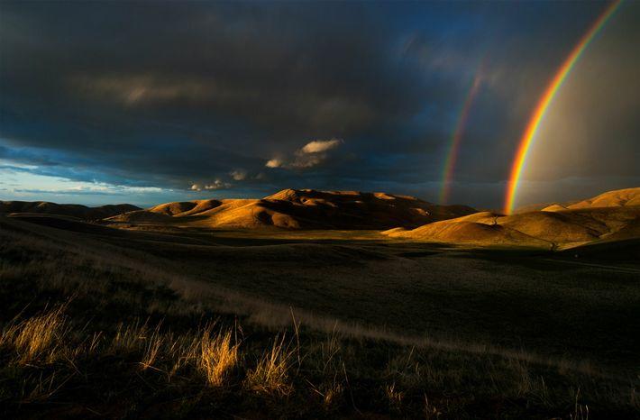 Regenbögen leuchten während eines Sturms im späten Frühling am Himmel über den kalifornischen San Emigdio Mountains. ...