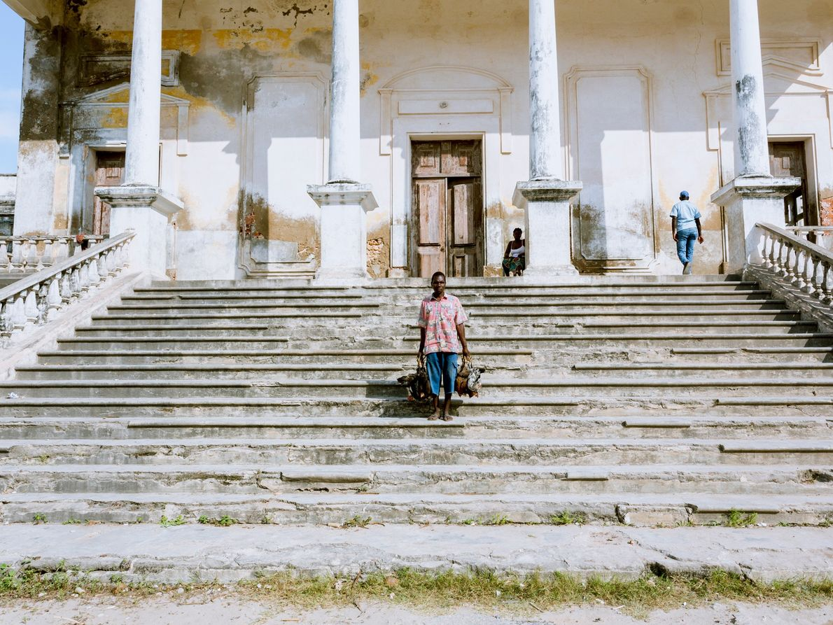 Ein Geflügelhändler posiert auf den Treppen des alten Krankenhauses, einem der schönsten und größten neoklassizistischen Gebäude ...