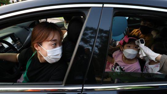 Eine Mutter sieht zu, wie die Temperatur ihrer Tochter in einer Durchfahrt-Klinik in Südkorea gemessen wird. ...
