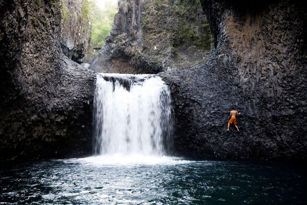 Kletterer an Felswand neben Wasserfall