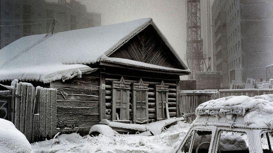 Ein traditionelles sibirisches Haus steht im Kontrast zu den neuen Bauten im Hintergrund. Trotz der Kälte ...