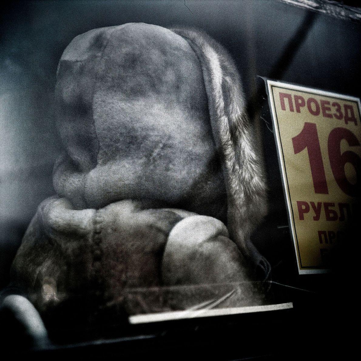 Eine Frau sitzt im Bus, eingehüllt in dicke Kleidungsschichten gegen die Kälte.