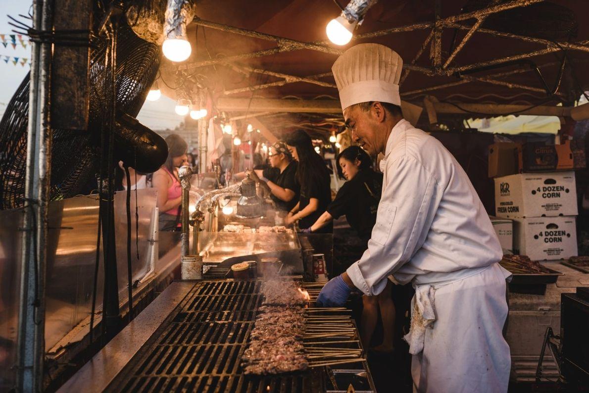 Ein Koch wendet sein Grillgut auf dem Richmond Night Market.