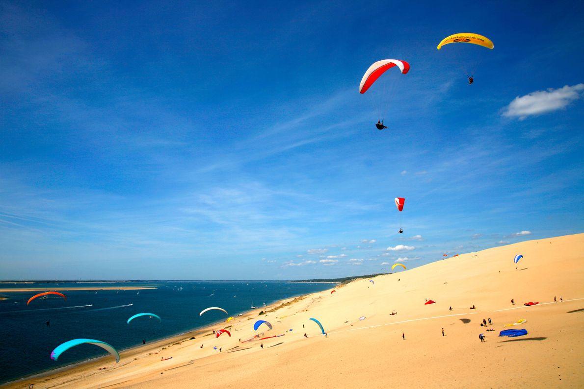 Foto eines Paragliders auf der Dune du Pilat über dem Strand von Corniche in La Teste-De-Buch, ...