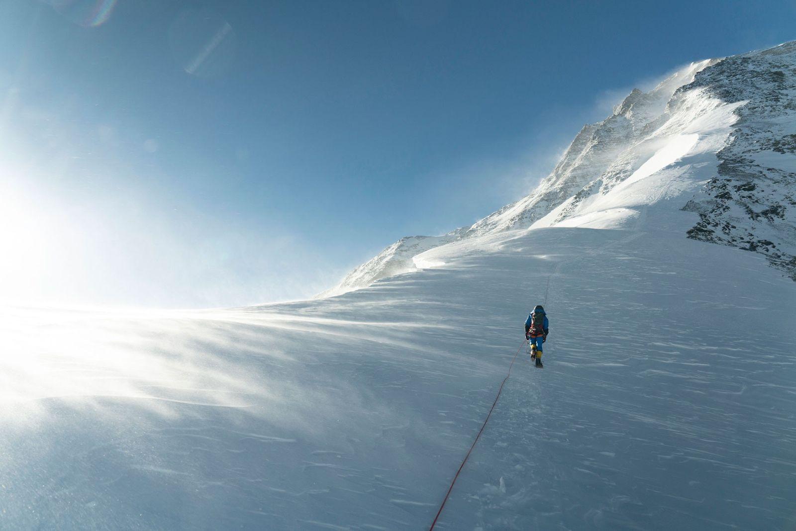 Ein Bergsteiger folgt bei starkem Wind der Normalroute auf dem Nordgrat des Everest. Der Wind wird ...