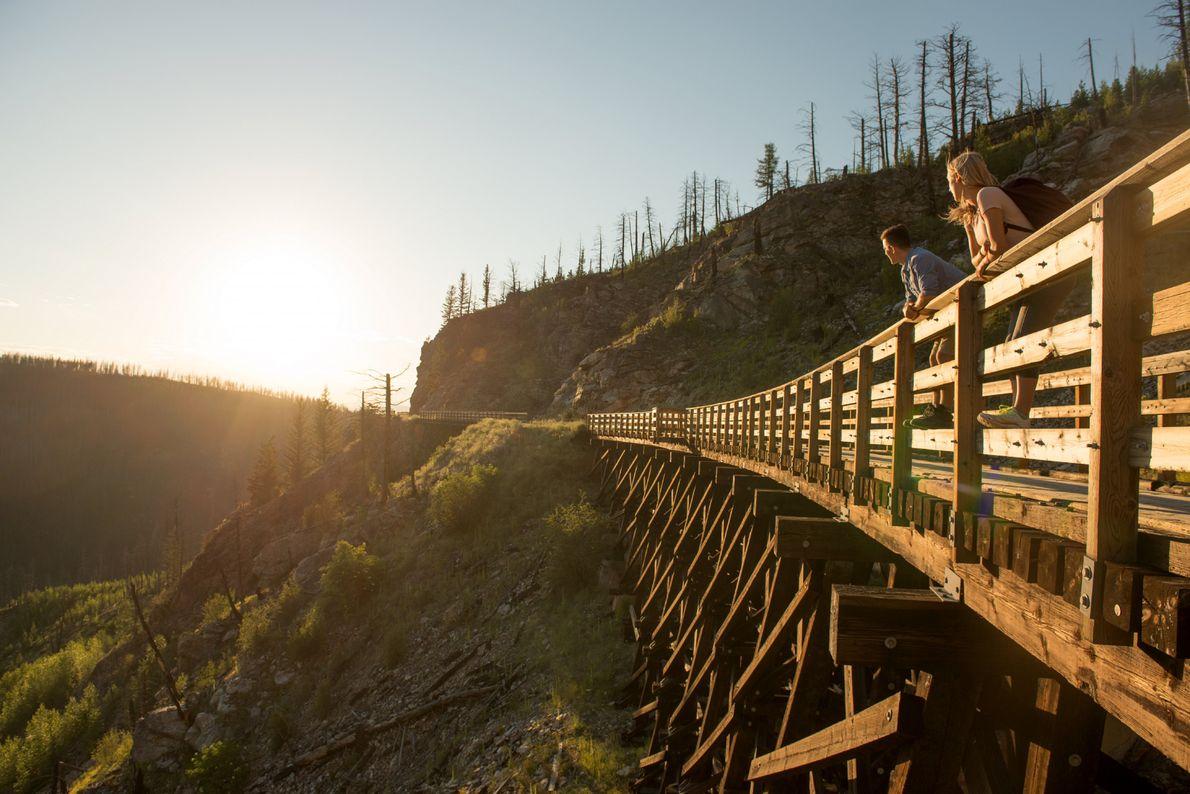 Ein Paar genießt den Sonnenuntergang auf einer der hölzernen Brücken des Kettle Valley Railway Trail über ...