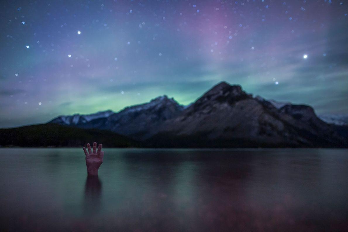 Eine Hand streckt sich aus dem Wasser des Lake Minnewanka im kanadischen Banff-Nationalpark.