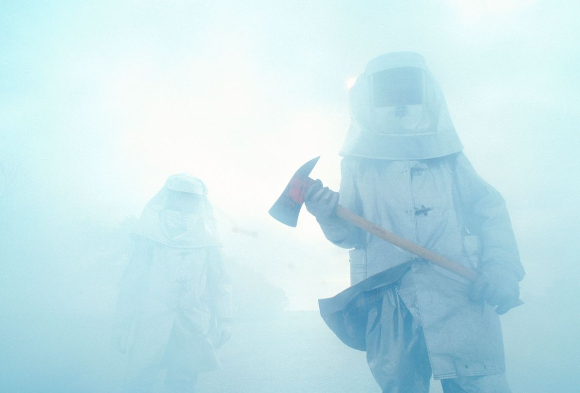 Feuerwehrmänner mit Äxten laufen durch eine dichte Rauchwolke in Texas.