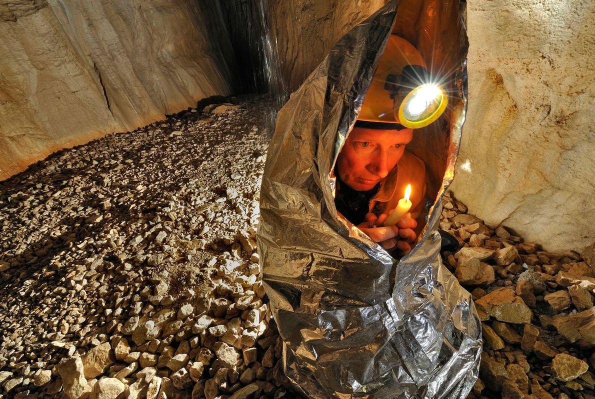 Ein Höhlenkletterer nutzt eine Kerze und eine Sicherheitsdecke, um in der Gouffre Berger warm zu bleiben. ...