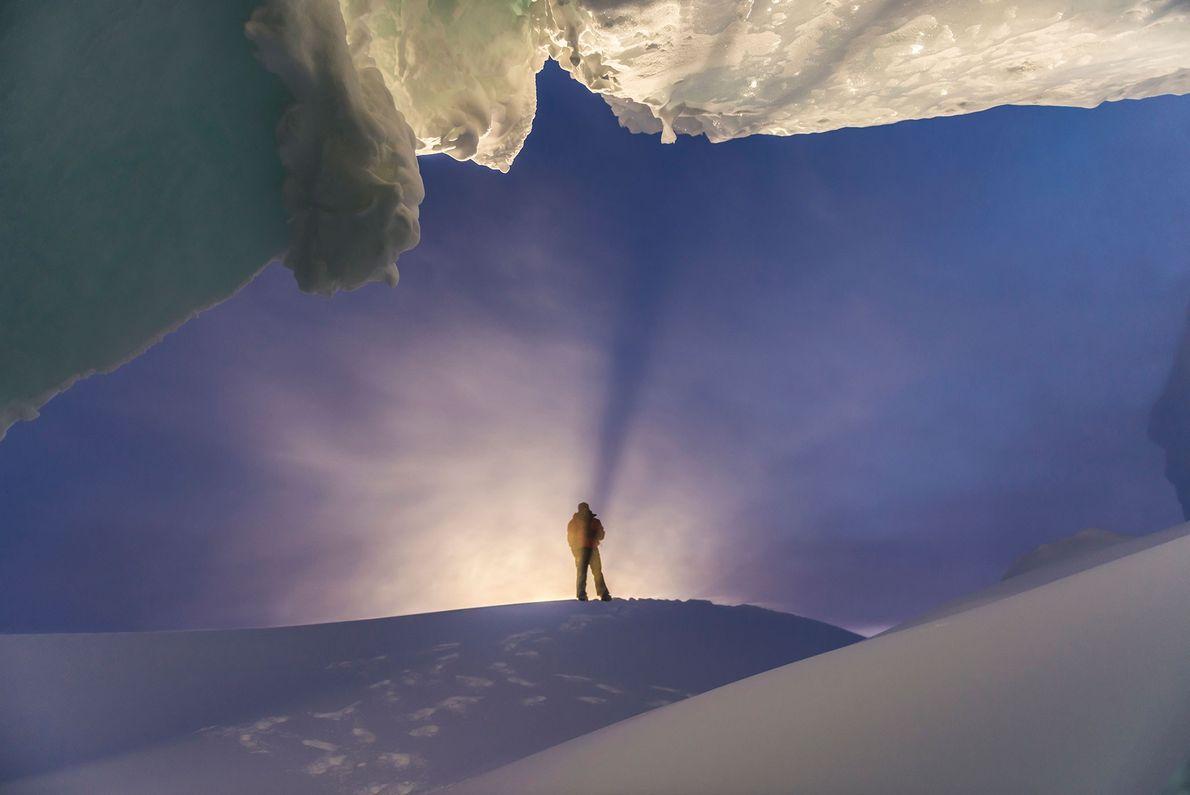 Ein Mann steht am Eingang einer Eishöhle in der Antarktis.