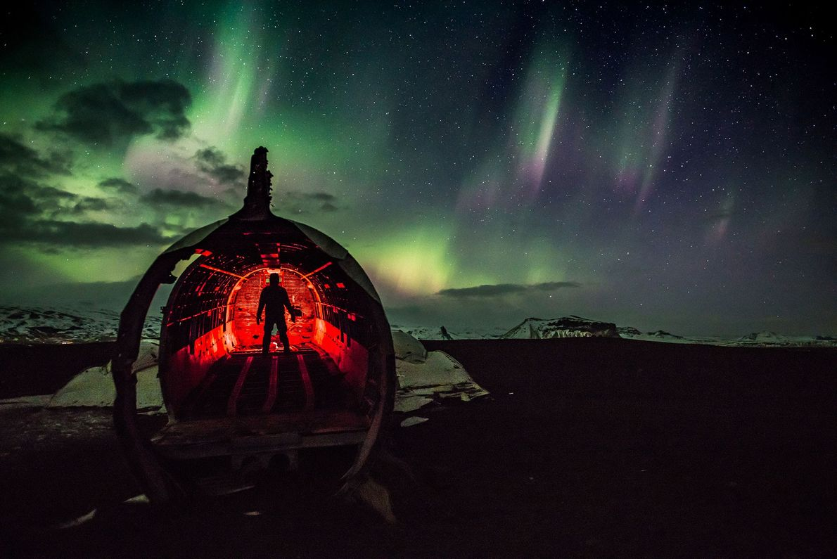 Ein Mann beleuchtet einen Teil eines Flugzeugwracks, das verlassen in der weiten Winterlandschaft Islands liegt. Über ...