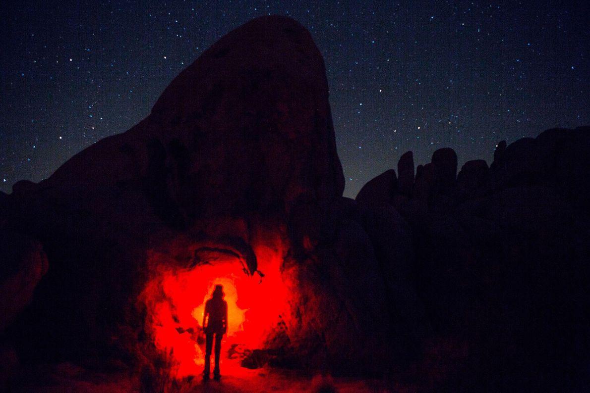 Ein Wanderer beleuchtet mit seiner Stirnlampe eine Felsformation im kalifornischen Joshua-Tree-Nationalpark.