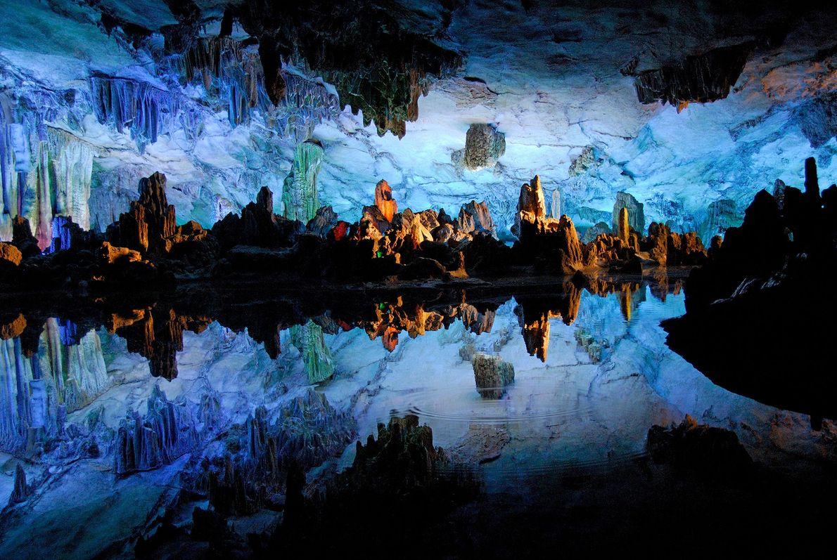Das glatte Wasser in der chinesischen Schilfrohrflötenhöhle in Guilin spiegelt die unheimlichen Felsformationen.