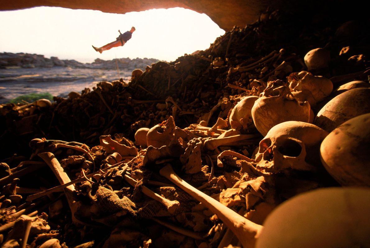 Ein Kletterer hängt am Eingang einer mit Knochen gefüllten Höhle an den Felsen von Bandiagara in ...