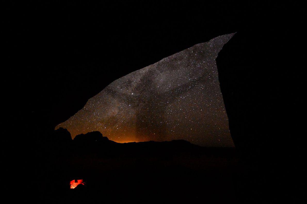 Der Schatten einer Person zeichnet sich vor dem Sternenhimmel über Namibia ab.