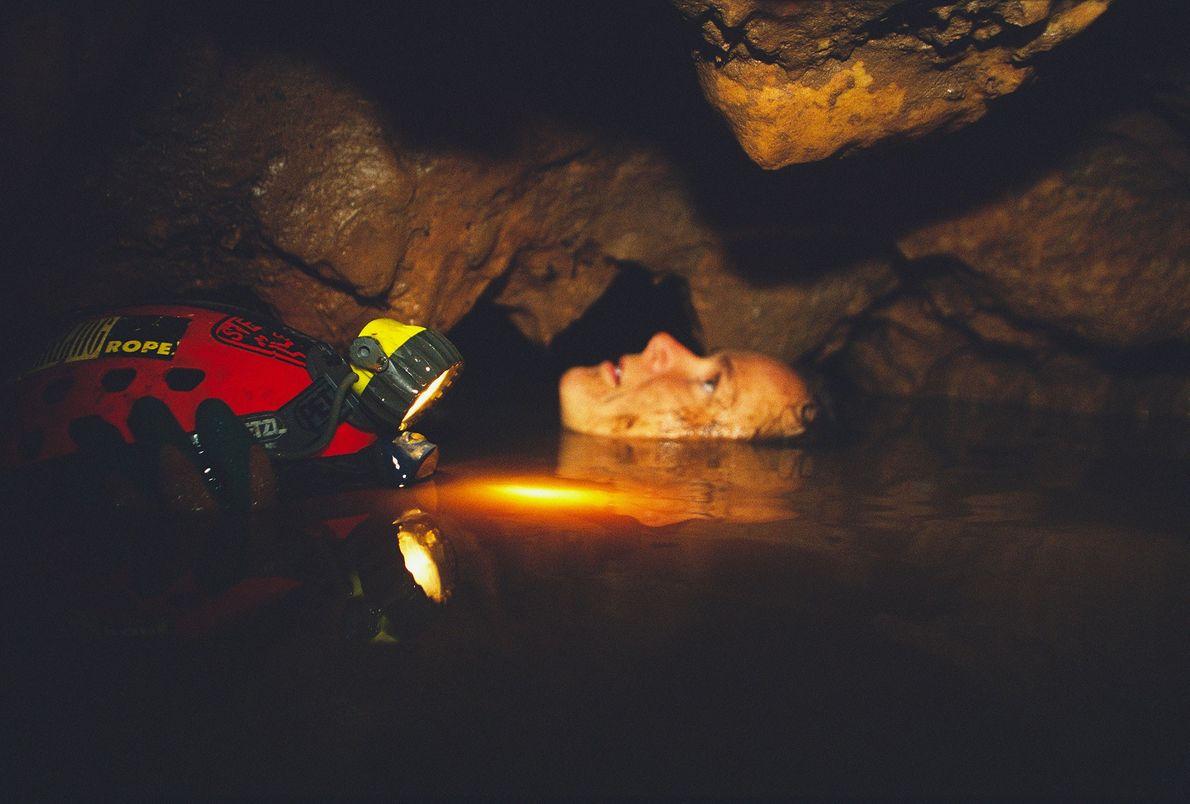 Eine Frau hält ihren Helm fest und schwimmt durch eine Engstelle in einer thailändischen Höhle.