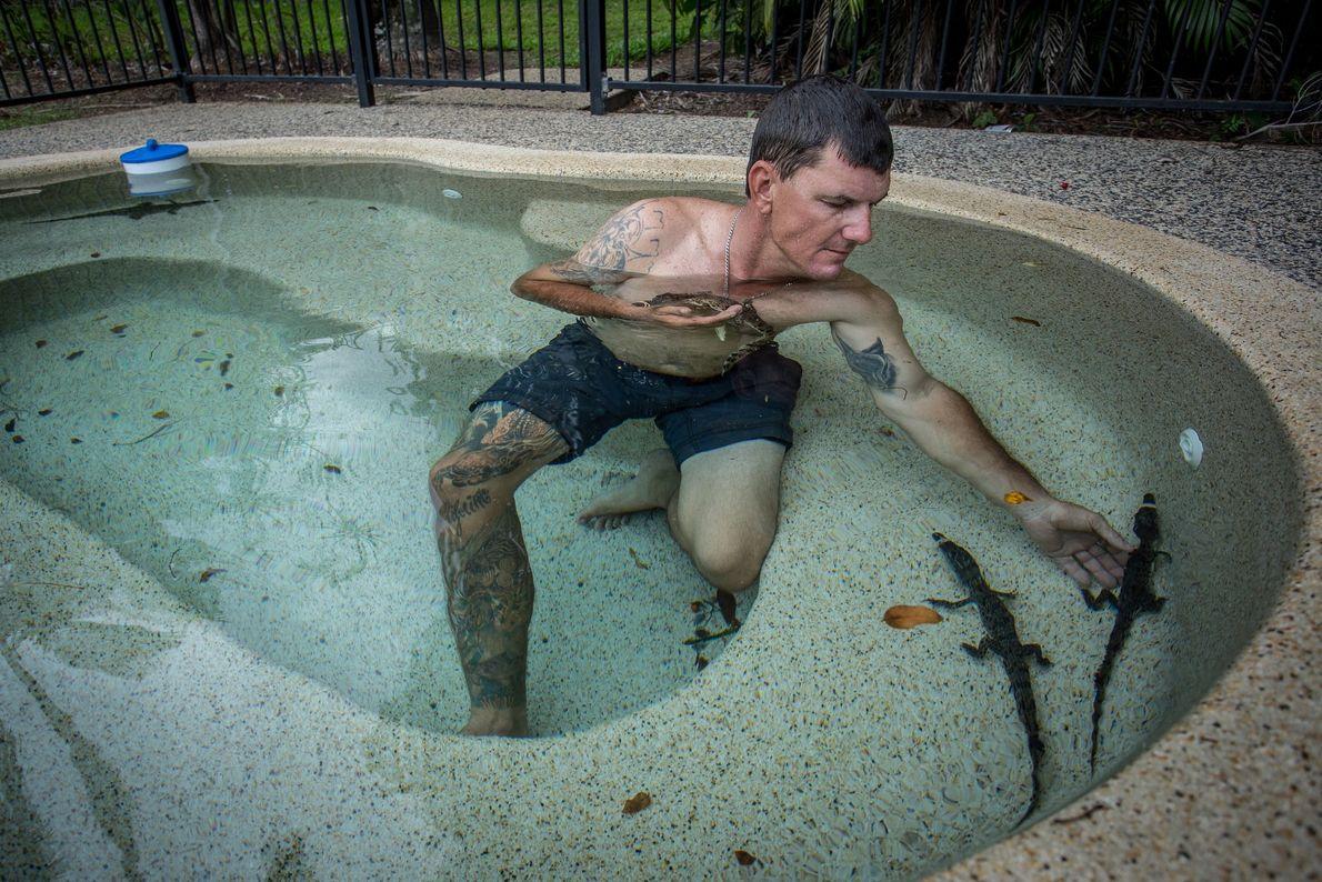 Mann badet mit kleinen Krokodilen