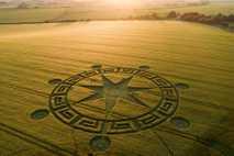 Die Sonne geht über einem Kornkreis in der Nähe von Sixpenny Handley im englischen Dorset unter.