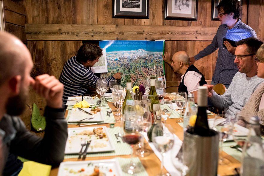 Tourenführer sehen sich mit der Tourengruppe beim Essen die geplante Route an.