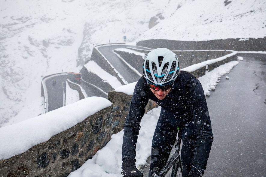 Ein Radfahrer fährt bei Schneefall durch die Dolomiten. Dort kann das Wetter rasch umschlagen.