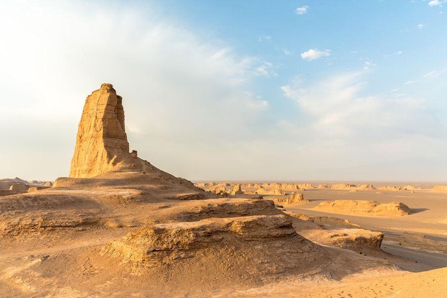 Eine Felsformation erhebt sich über dem Wüstenboden in Dasht-e Lut, Iran.