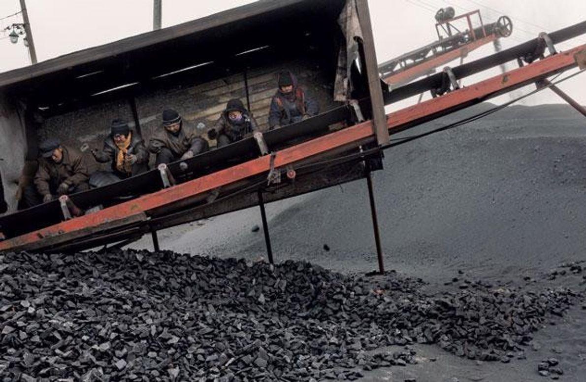 An einer Verladestation lesen Arbeiter vom Förderband vor ihnen Steine aus der Kohle – oft ohne …