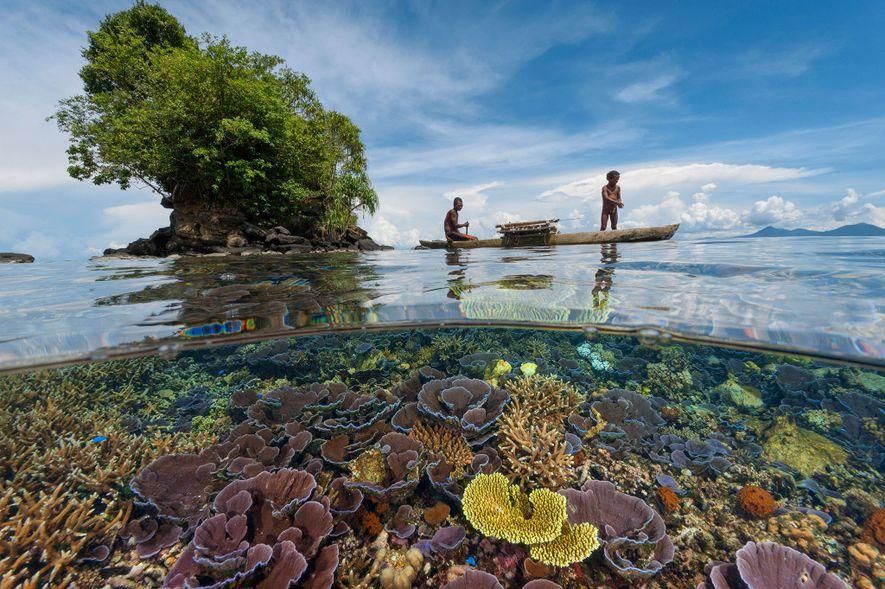 Zwei Fischer – Vater und Sohn – gleiten im Windschatten einer kleinen Insel der Kimbe Bay ...