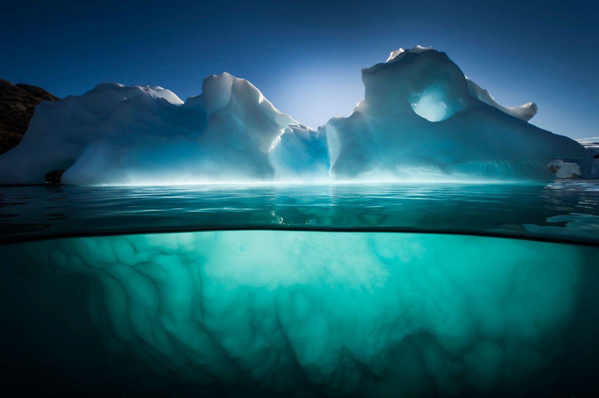 Ein Eisberg leuchtet im Nachmittagslicht bei Red Island im Fjord von Kangertittivaq in Grönland. Eisberge sind ...